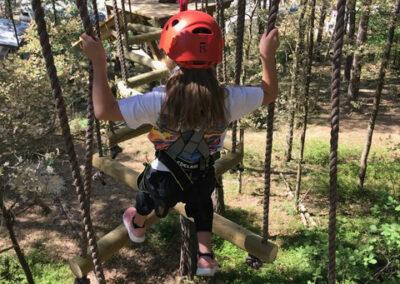 Barn med röd hjälm klättrar i höghöjdsbana.