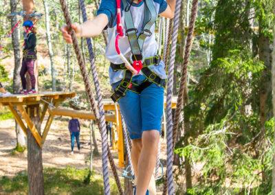 Barn går balansgång över en hängande sten i höghöjdsbana.