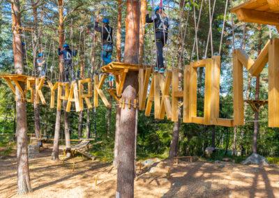 Familj och vänner klättrar igenom en höghöjdsbana med hängande bokstäver i Skypark Vaxholm.