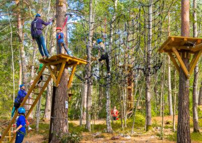 Familj klättrar genom ett av äventyrsparken Skypark Vaxholms många rephinder.
