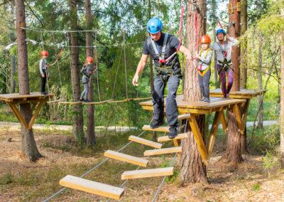 Familj tar sig igenom en av testbanorna på äventyrsparken Skypark Vaxholm.