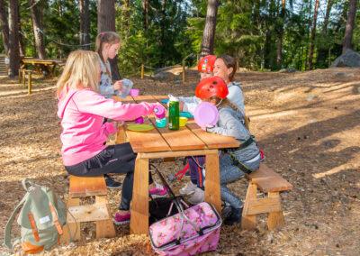 Familj äter picknick på en bänk i äventyrsparken.