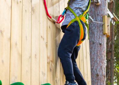 Liten flicka på en klättervägg i äventyrsparken Skypark Vaxholm.