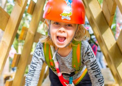 Glad liten flicka på en hängande plattform i äventyrsparken Skypark Vaxholm.