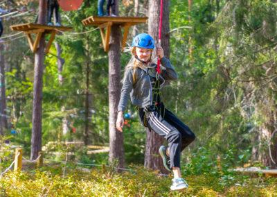Glad flicka åker zip-line på äventyrsparken Skypark Vaxholm.