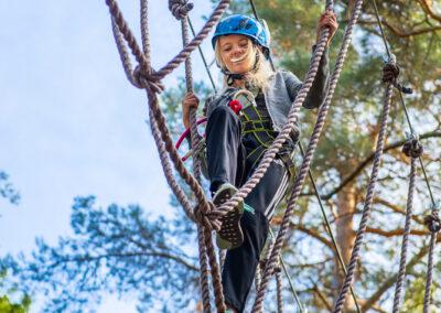 Glad tjej tar sig igenom ett rephinder i äventyrsparken Skypark Vaxholm.