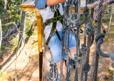 Glad ung kille klättrar i ett hängande nät på Skypark.