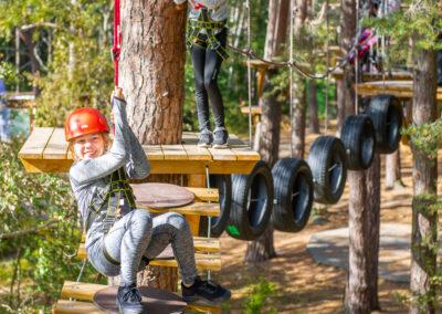 Glad ung tjej hänger i ett säkerhetsrep efter att ha tappat balansen.