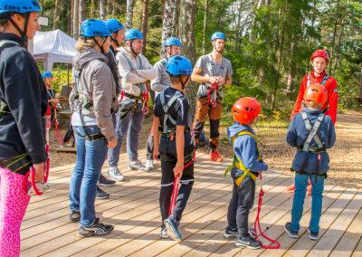 Instruktör går igenom säkerhet i äventyrsparken.