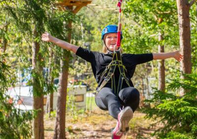 Skrattande kvinna åker zipline i skogen.