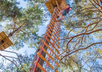Tonåring klättrar upp i via en repstege till höghöjdsbanan.