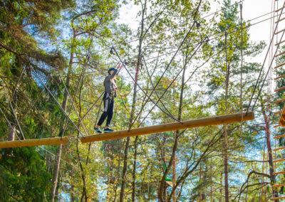 Ung tjej balanserar sin väg genom en hängande stock i äventyrsparken Skypark Vaxholm.