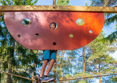 Boy smiling at the camera during his adventure at the adventure park SkyPark Vaxholm.
