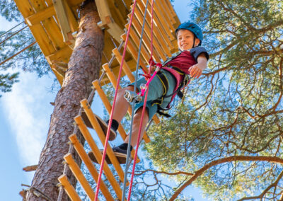 Child climbing a ladder at an adventure park.