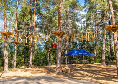 Children climbing their way through an adventure track with hanging wooden letter in Skypark Vaxholm.