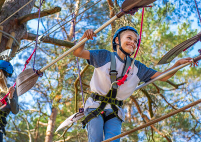Happy boy climbing his way through a rope hurdle in the adventure park Skypark Vaxholm