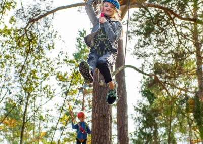 Happy girl riding a zip-line at the adventure park Skypark Vaxholm.