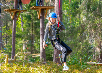Happy girl during her zip-line ride at the adventure park Skypark Vaxholm.