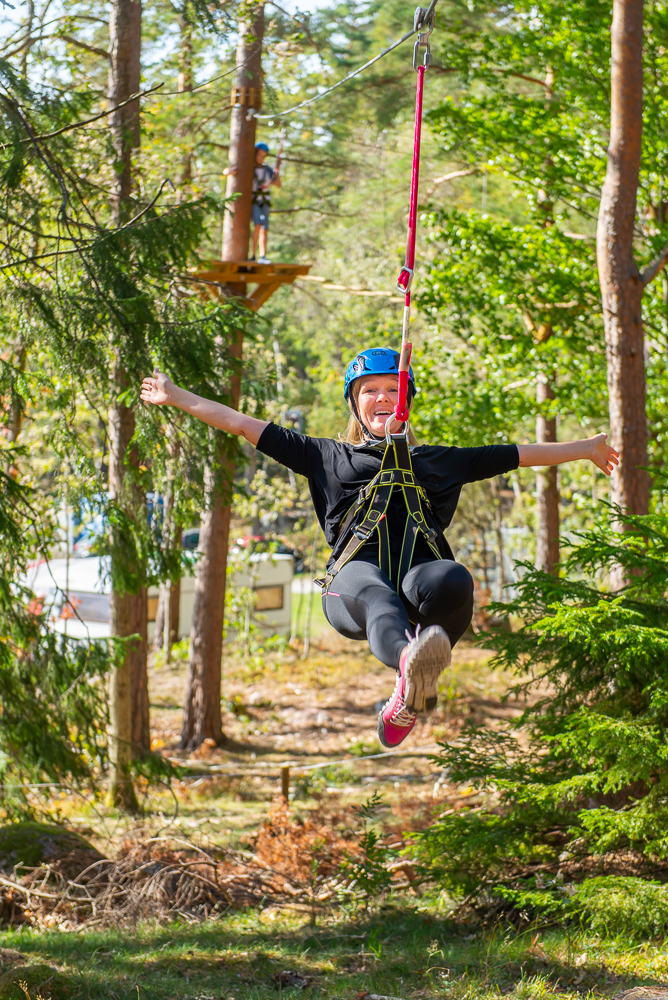 Happy woman riding a zipline in nature.