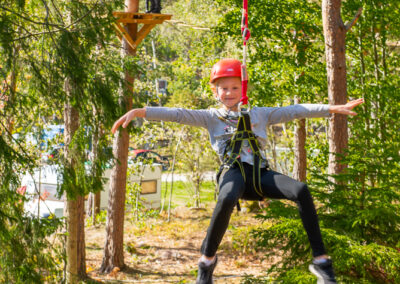 Smiling child riding zipline in the forest at Skypark.
