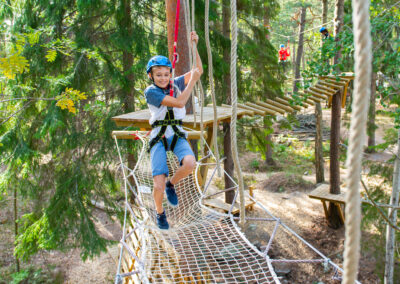 Young boy smiling while climbing trough an adventure track.